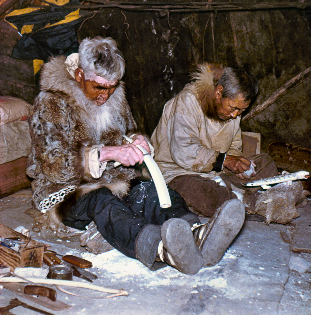 1950s Carving ivory. Kotzebue, AK. Wearing beaver skin parka with wolf ruff. Ruffon right is wolverine skin.