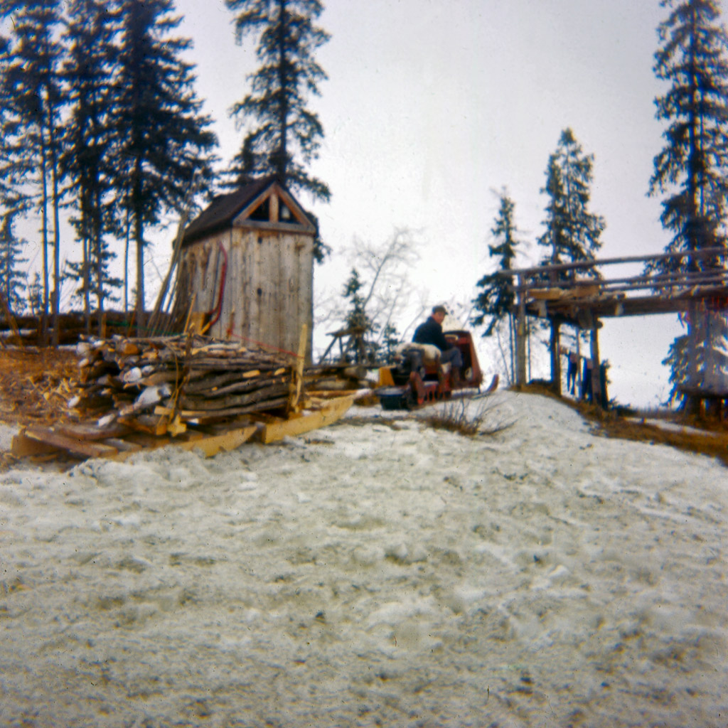 1960s Gary Bringing in a load of wood with our snow traveler. Outhouse in background.