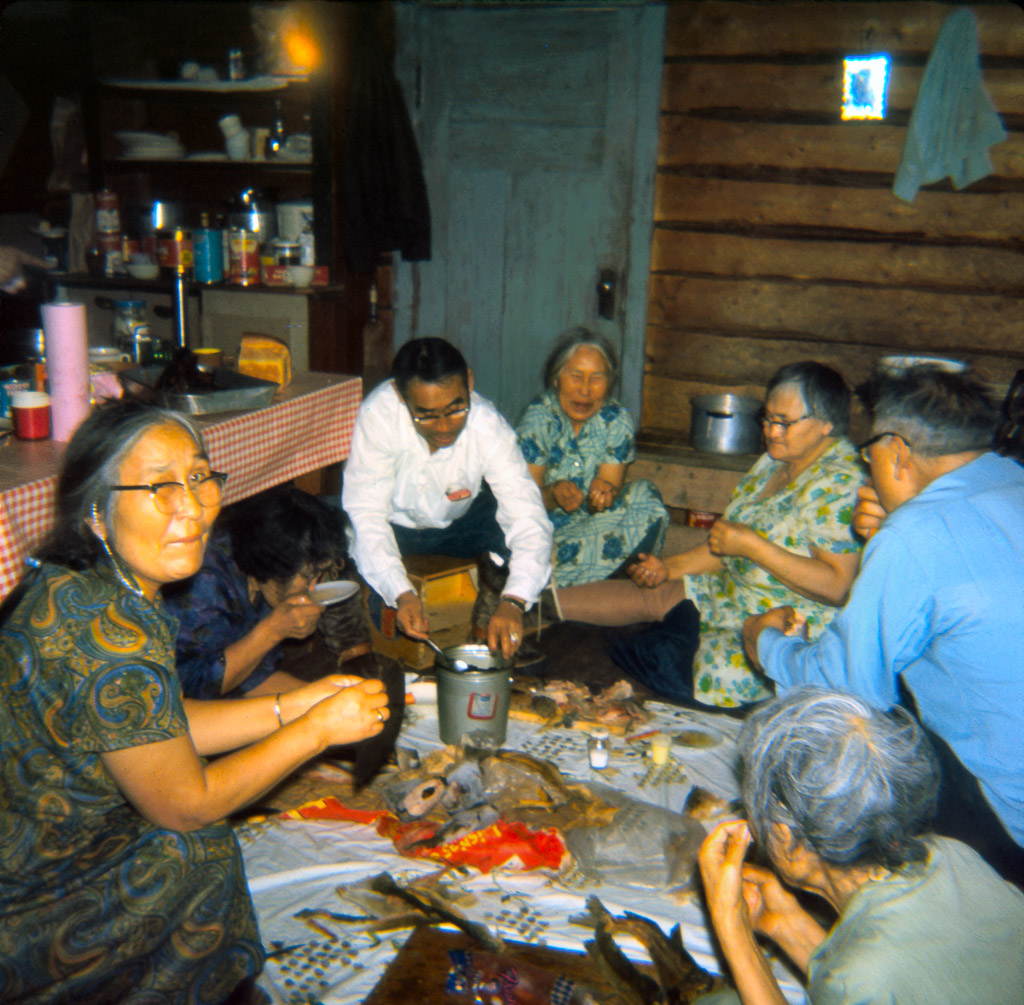 1960s Meal time in Kiana.  Dora Johnson on the left.  Eating frozen fish, dried fish, and seal oil.