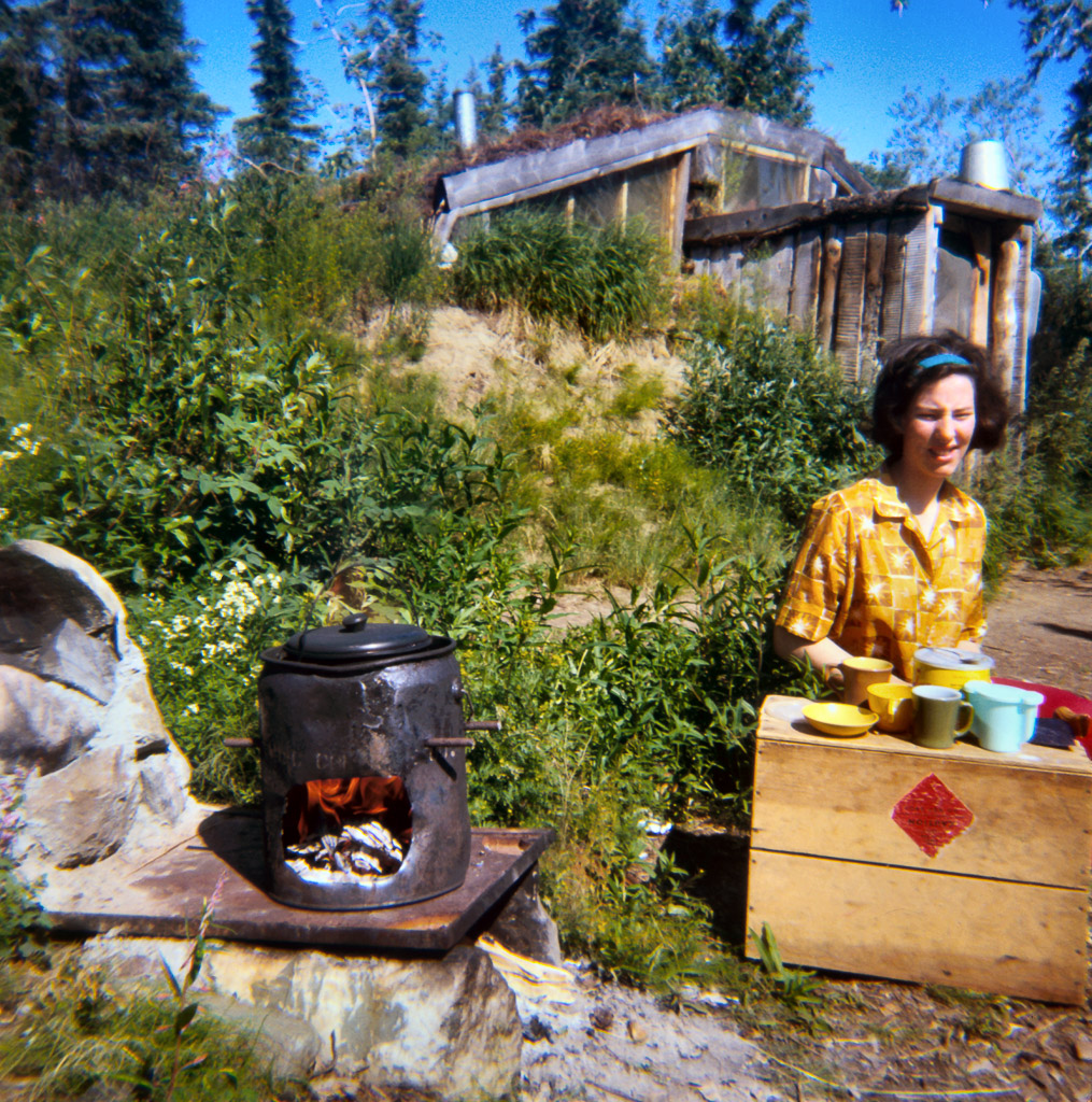 1969 Dorene cooking breakfast. Outdoor stove in front of our house. Using Blazo box as a table.