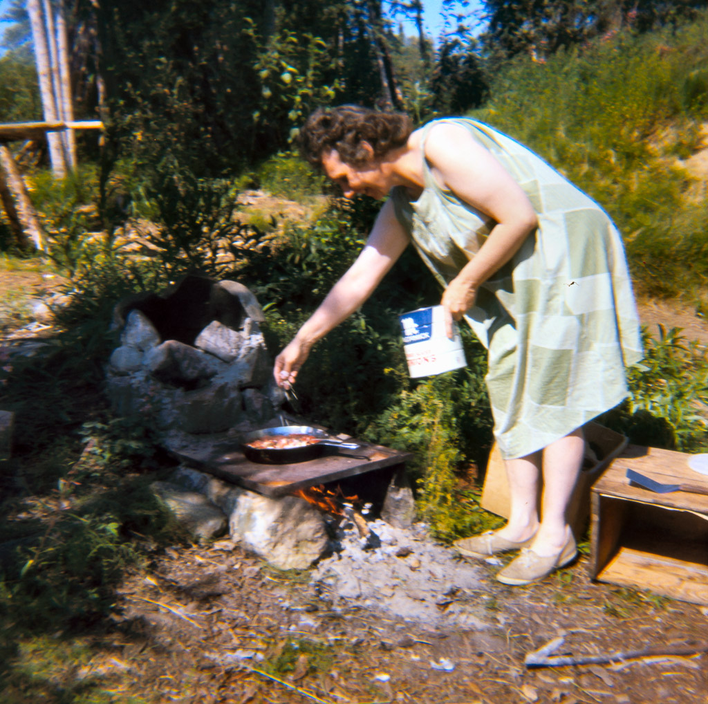 1969 Mama Lorene cooking breakfast on outdoor stove.