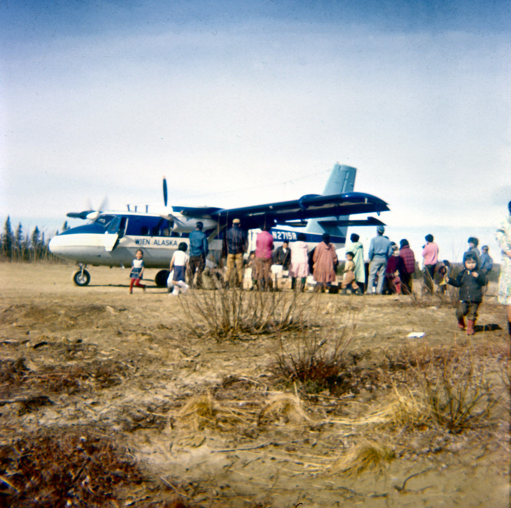 Late 1060s. Twin Otter mail plane on dirt strip behind town.