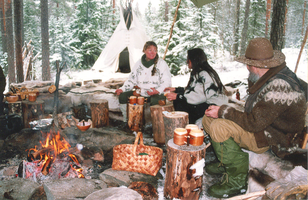Oliver, Heidi and one other sitting around campfire. Teepee in background. Norway