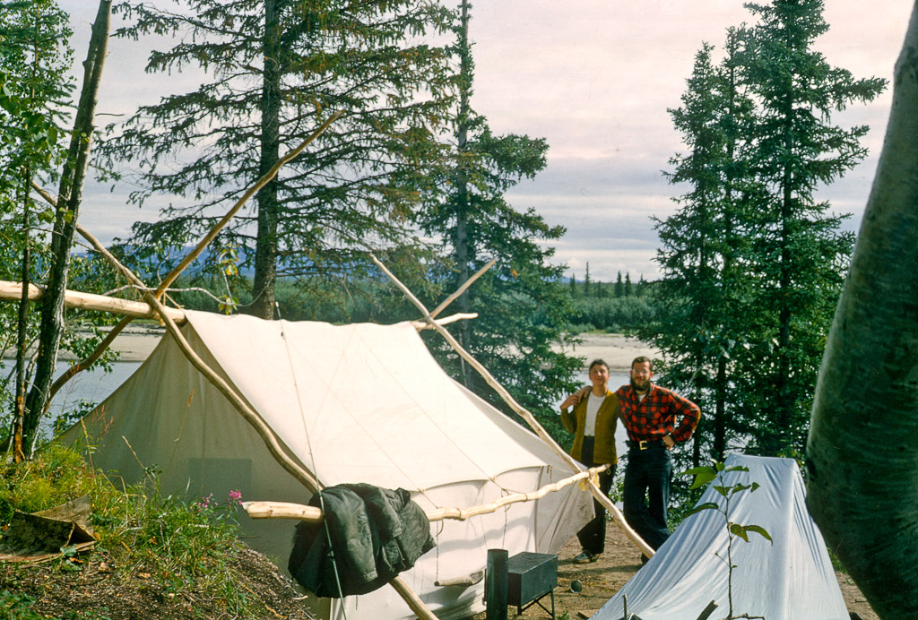Joyce and Dan Denslow in front of white wall tent.  Ambler River in the background, small wood stove beside the tent.